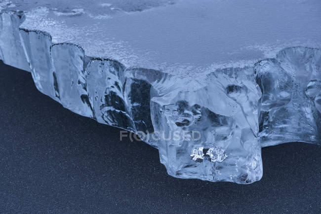 Primo piano di un pezzo di ghiaccio seduto nella sabbia nera sulla riva meridionale dell'Islanda; Islanda — Foto stock