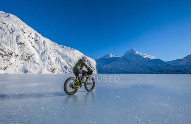 Uomo in sella fatbike attraverso congelato Portage Lake a metà inverno nel centro-sud Alaska, Stati Uniti d'America — Foto stock