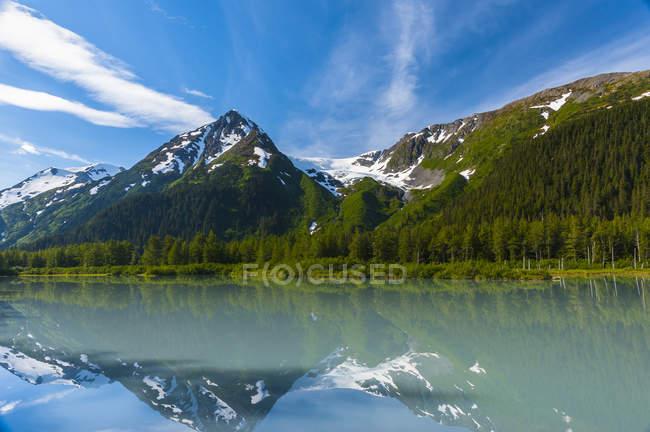Explorer glacier reflektiert im ruhigen wasser des explorer lake an einem sonnigen sommermorgen im portage tal, alaska, vereinigte staaten von amerika — Stockfoto