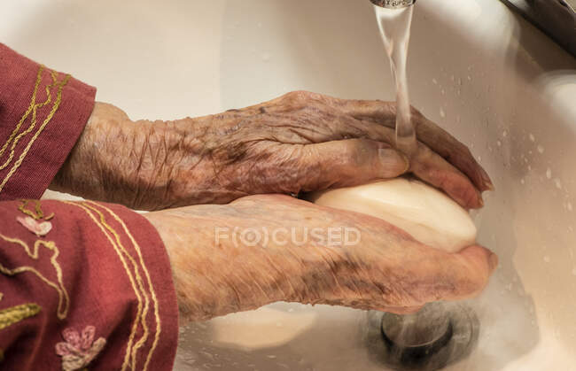 Senior woman washing her hands — Stock Photo