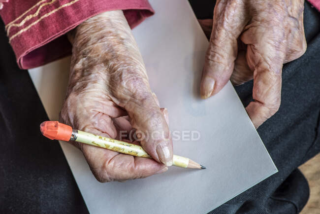 Senior woman hands getting ready to write a note with a pencil — Stock Photo