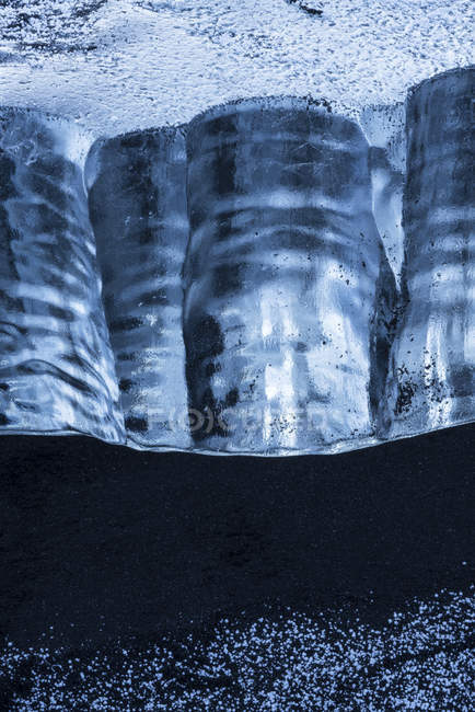 Close-up of a piece of ice sitting in the black sand on the South shore of Iceland; Iceland — Stock Photo