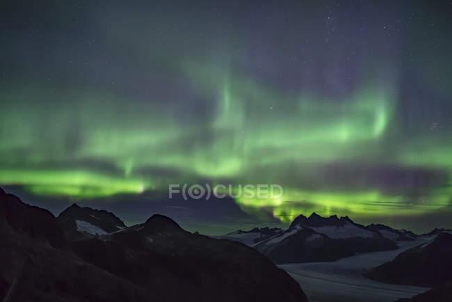 Luces boreales que brillan sobre el campo de hielo de Juneau, bosque nacional de Tongass; Alaska, Estados Unidos de América - foto de stock