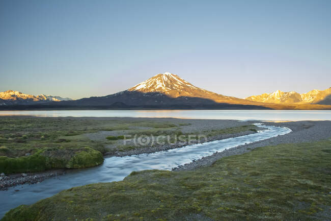 A stream leading towards a high altitude lake. A volcano and snow-capped mountains in the distance are lit by the sunrise against a pure blue sky; Mendoza, Argentina — Stock Photo