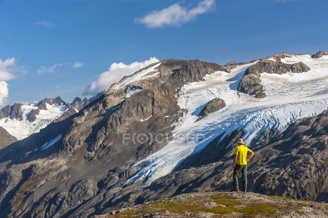 Rear view of hiker in hat looking out at Kenai Fjords National Park, Kenai Peninsula, Alaska, United States of America — Stock Photo