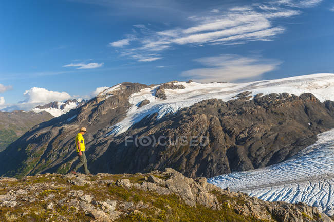 Man hiking near the Harding Icefield Trail with the Kenai Mountains and an unnamed hanging glacier in the background, Kenai Fjords National Park, Kenai Peninsula, South-central Alaska, United States of America — Stock Photo