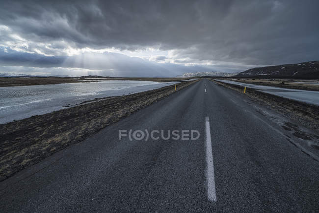 Road leading into the dramatic landscape of Iceland while the sun shines through the clouds making a beautiful scene; Iceland — Stock Photo