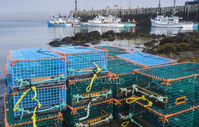 Casiers à homards empilés le long du rivage avec des bateaux attachés à un quai en arrière-plan, baie de Fundy ; Tiverton, Long Island, Nouvelle-Écosse, Canada — Photo de stock