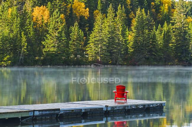 Стільце на пристані з осінньо-барвистим листям відбите в спокійному озерному озері, національний парк Riding Mountain National Park; Манітоба (Канада). — стокове фото