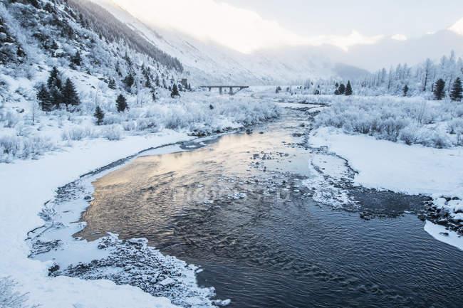 Río que fluye a través de un paisaje nevado y montañoso al amanecer; Alaska, Estados Unidos de América - foto de stock