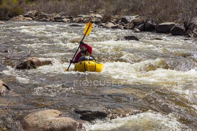 Femmina packrafter negoziare una rapida tecnica sul affluente del fiume Charley in estate; Alaska, Stati Uniti d'America — Foto stock