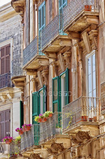 Fassade eines Wohnhauses mit Rollläden und Balkonen; Syrakus, Sizilien, Ortigia, Italien — Stockfoto