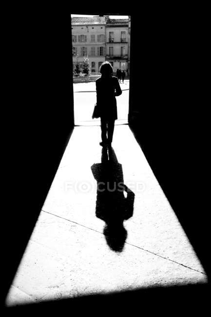Silhouette and shadow of a woman going through a doorway to a town square towards City Hall; Arles, Provence Alpes Cote D'Azur, France — Stock Photo