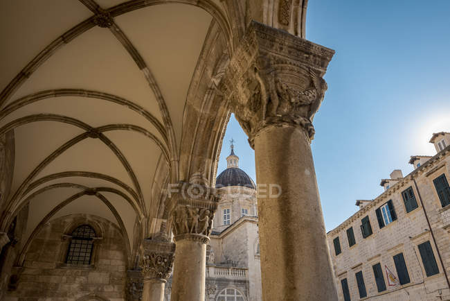 Detail of columns in the Rectors Palace facade and the Cathedral in the background; Dubrovnik, Dubrovnik-Neretva County, Croatia — Stock Photo