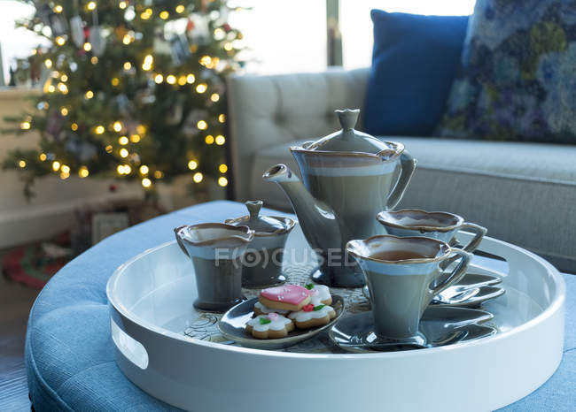 Tea served on a tray with cookies and a Christmas tree in the background at Christmas; Surrey, British Columbia, Canada — Stock Photo