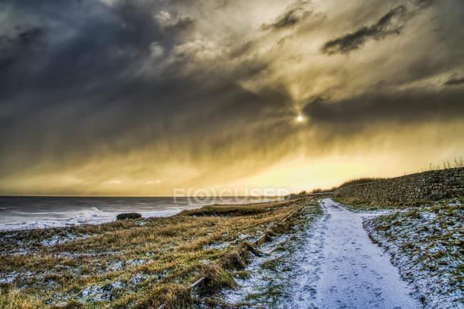 Sentier enneigé le long de la côte avec un soleil doré illuminant les nuages, South Shields, Tyne and Wear, Angleterre — Photo de stock