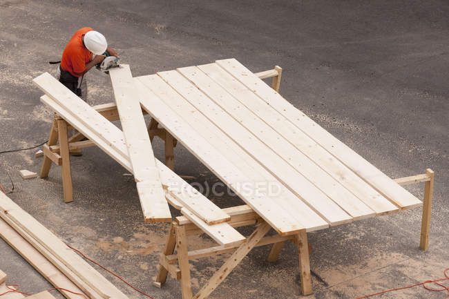 High angle view of a carpenter cutting bevels on rafters — Stock Photo
