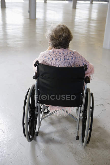 Rear view of an old woman sitting in the wheelchair - Staged — Stock Photo