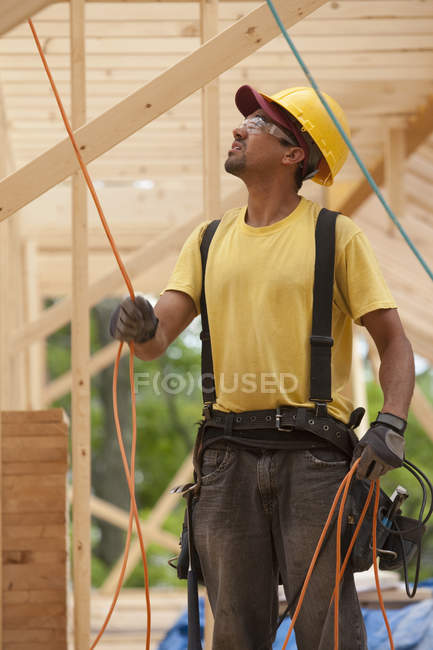 Carpenter arranging power cords at building construction site — Stock Photo