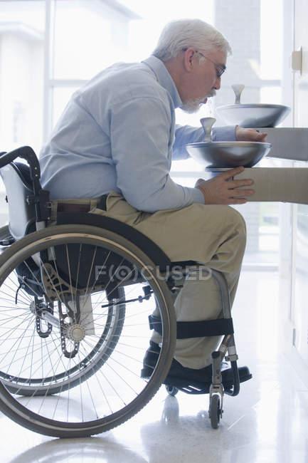 Професор університету з м'язової дистрофії сидить у інвалідному візку і питної води з фонтану — стокове фото