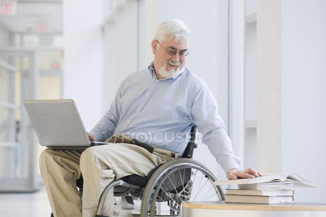 Університет професора з м'язової дистрофії читанні книги і використання ноутбука — стокове фото