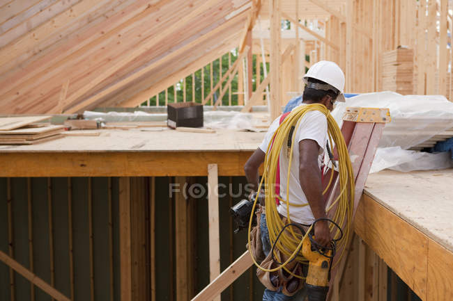 Carpenter moving tools down ladder at end of day to go home — Stock Photo