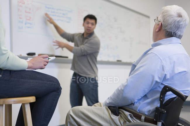 Profesora universitaria con distrofia muscular que enseña a los estudiantes en un aula - foto de stock