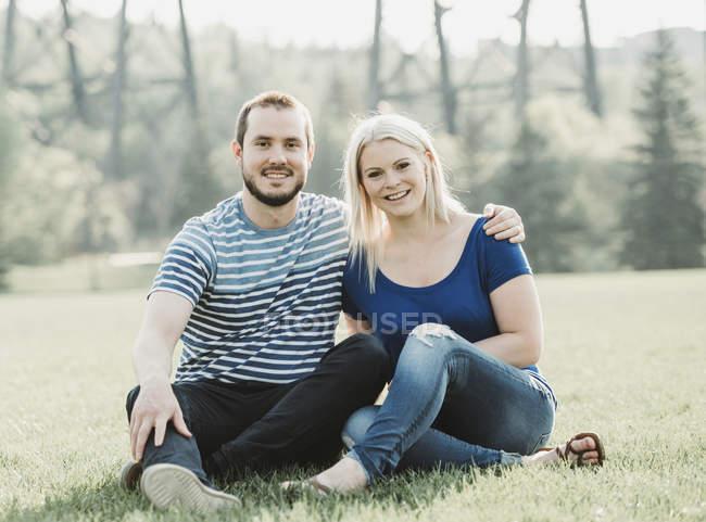 Портрет пары в парке, сидящей на траве; Эдмонтон, Альберта, Канада — стоковое фото