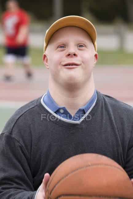 Человек с синдромом Дауна играет в баскетбол — стоковое фото