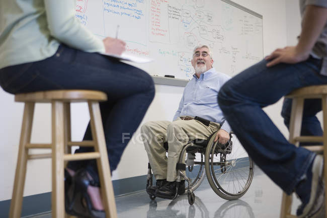 University professor with Muscular Dystrophy teaching students in a classroom — Stock Photo