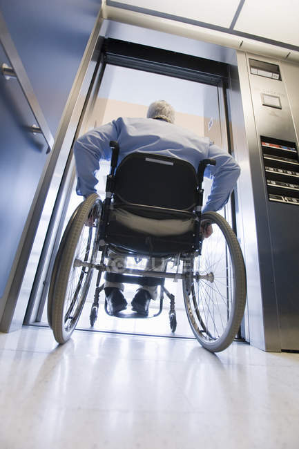 University professor with Muscular Dystrophy in a wheelchair entering an elevator — Stock Photo