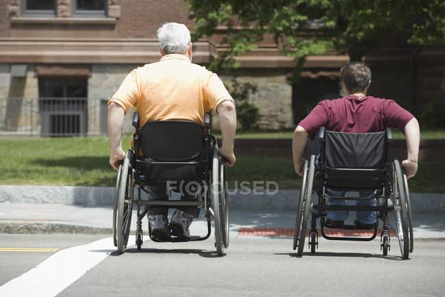Vista posteriore di un uomo maturo con distrofia muscolare e una giovane donna che attraversa una strada in sedie a rotelle — Foto stock