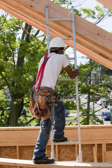 Carpenter climbing a ladder at building construction site — Stock Photo