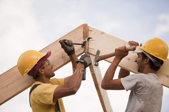 Carpenters adjusting rafters with hammer and nails and pry bar — Stock Photo