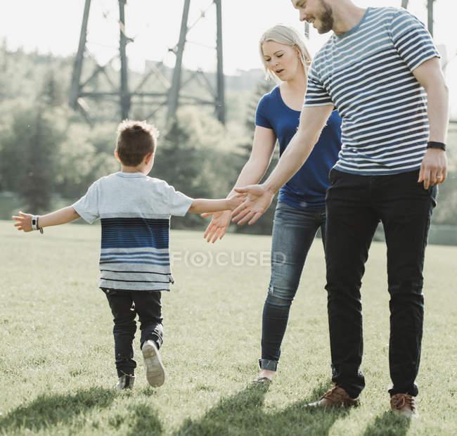 Una familia con un hijo pequeño jugando en un parque; Edmonton, Alberta, Canadá - foto de stock