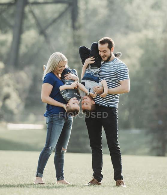 Una familia con niños pequeños jugando en un parque; Edmonton, Alberta, Canadá - foto de stock