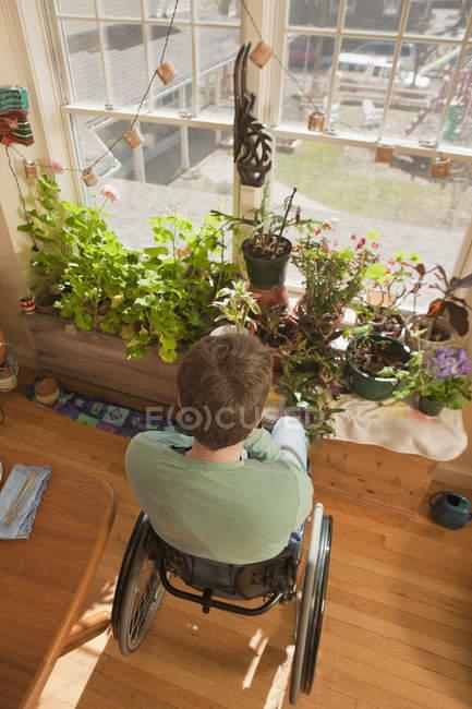 Mulher com esclerose múltipla em uma cadeira de rodas olhando para fora da janela de sua casa acessível — Fotografia de Stock