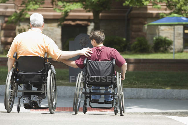 Vista posteriore di un uomo di mezza età e una donna di mezza età con distrofia muscolare che attraversa una strada in sedie a rotelle — Foto stock