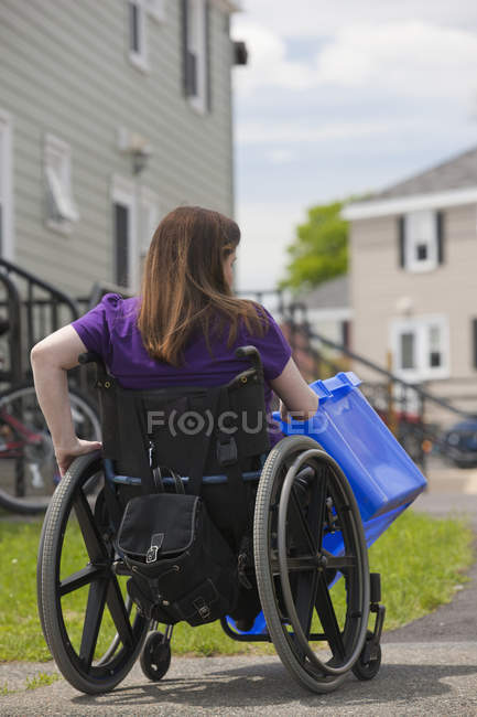 Woman with Spina Bifida in a wheelchair picking up a recycling bin at the street — Stock Photo