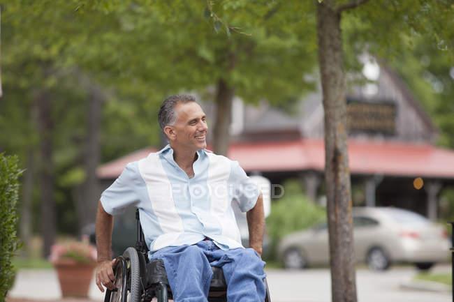 Homme avec lésion de la moelle épinière dans un fauteuil roulant faire du shopping — Photo de stock