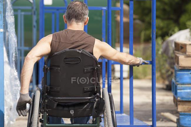 Carregando o trabalhador portuário com lesão medular em uma cadeira de rodas movendo um caminhão de mão — Fotografia de Stock