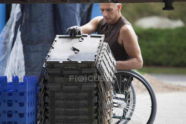 Chargement docker avec lésion de la moelle épinière dans un fauteuil roulant mobiles plateaux d'inventaire empilés — Photo de stock