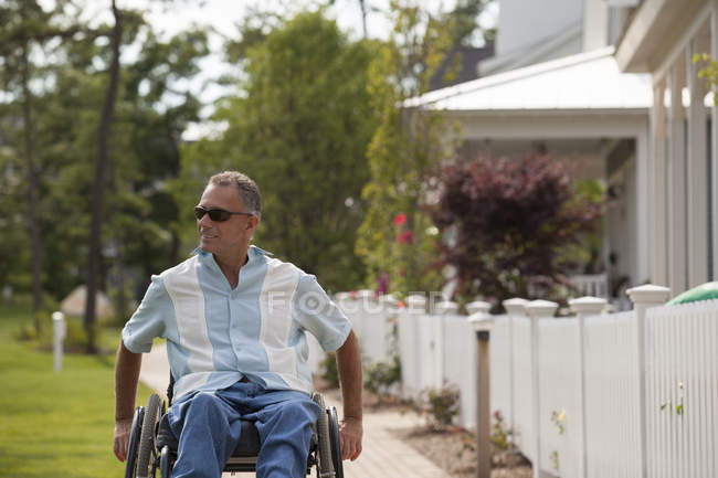 Man with spinal cord injury in a wheelchair on a suburb walk with homes — Stock Photo
