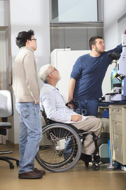 Profesor con distrofia muscular trabajando con estudiantes en un laboratorio - foto de stock
