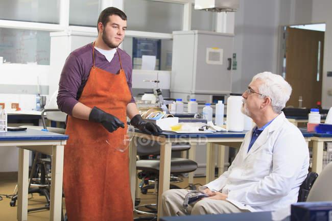 Profesor con distrofia muscular trabajando con el estudiante en un laboratorio - foto de stock