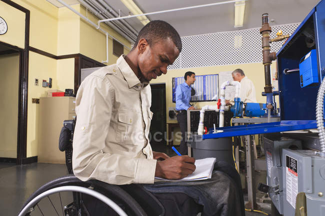 Student in wheelchair studying furnace electronic control system in HVAC classroom — Stock Photo