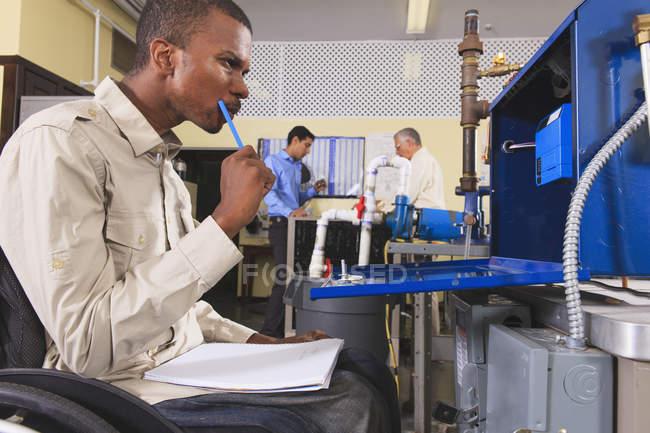 Étudiant en fauteuil roulant étudiant le système de contrôle électronique de four dans la salle de classe CVC — Photo de stock
