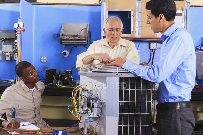 Instructeur formant les étudiants sur les unités de climatisation dans la salle de classe CVC — Photo de stock