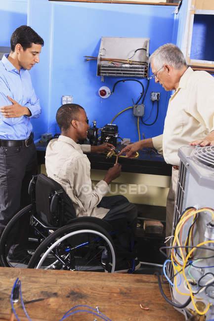 Інструктор обговорює конденсаторну котушку на холодильнику з студентом у інвалідному візку. — стокове фото