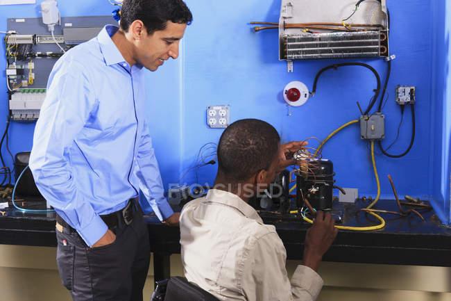 Étudiants examinant la bobine de condensateur sur l'unité de réfrigération dans la salle de classe CVC — Photo de stock
